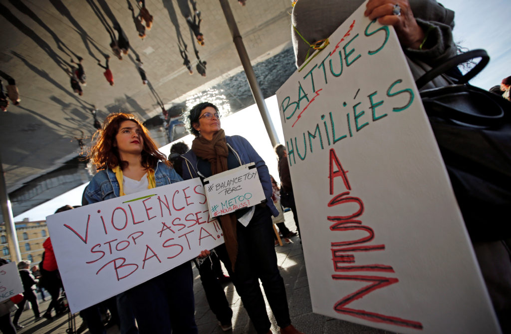 """Women hold placards reading, """"Violence. Stop. Enough!"""", """"Humiliated. Beaten. Enough"""" and the name-and-shame hashtag #BalanceTonPorc - or 'expose your pig', during a gathering against gender-based and sexual violence in Marseille, France, October 29, 2017. REUTERS/Jean-Paul Pelissier"""