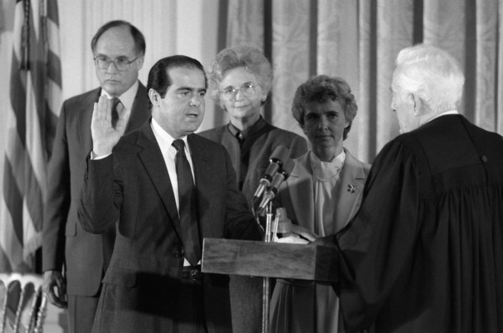 Antonin Scalia is sworn in as associate justice of the Supreme Court by Chief Justice Warren Burger, (R), at the White House, 9/26. Looking on are (L to R), William Rehnquist, Mrs. Rehnquist and Mrs. Scalia.