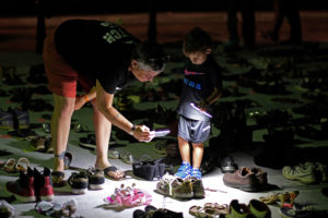 A woman and child photograph shoes displayed in memory of those killed by Hurricane Maria, on display in front of the Puerto Rican capitol in San Juan in June, 2018. Photo by Ricardo Arduengo AFP/Getty Images