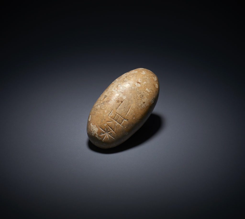 A polished river pebble appears to have an inscription in Old Sumerian script. Photo courtesy of the British Museum