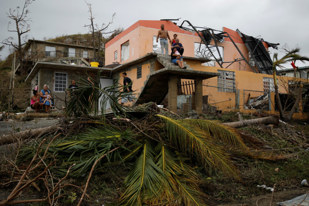 People rest outside a damaged house after the area was hit by Hurricane Maria in Yabucoa, Puerto Rico on September 22, 201...