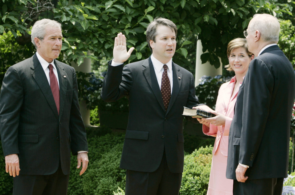 U.S. President George W. Bush (L) watches as Brett Kavanaugh (2nd L) is sworn in as a judge in the U.S. Court of Appeals for the District of Columbia by Supreme Court Associate Justice Anthony Kennedy (R) in a Rose Garden ceremony at the White House in Washington June 1, 2006. Kavanaugh's wife, Ashley, holds the bible.  REUTERS/Larry Downing  (UNITED STATES) - GM1DSSTWUSAA