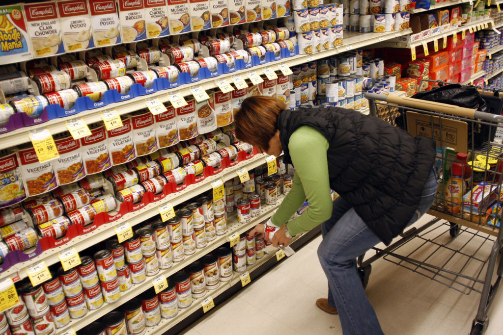 A customer grabs cans of Campbell's Soup from a shelf at a grocery store in Phoenix, Arizona. Photo by Joshua Lott/Reuters