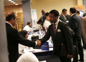 A job seeker meets with a prospective employer at a career fair in New York City, October 24, 2012. Despite the economic recovery, workers today are paid less today than they were a decade ago, when earnings are adjusted for inflation. REUTERS/Mike Segar