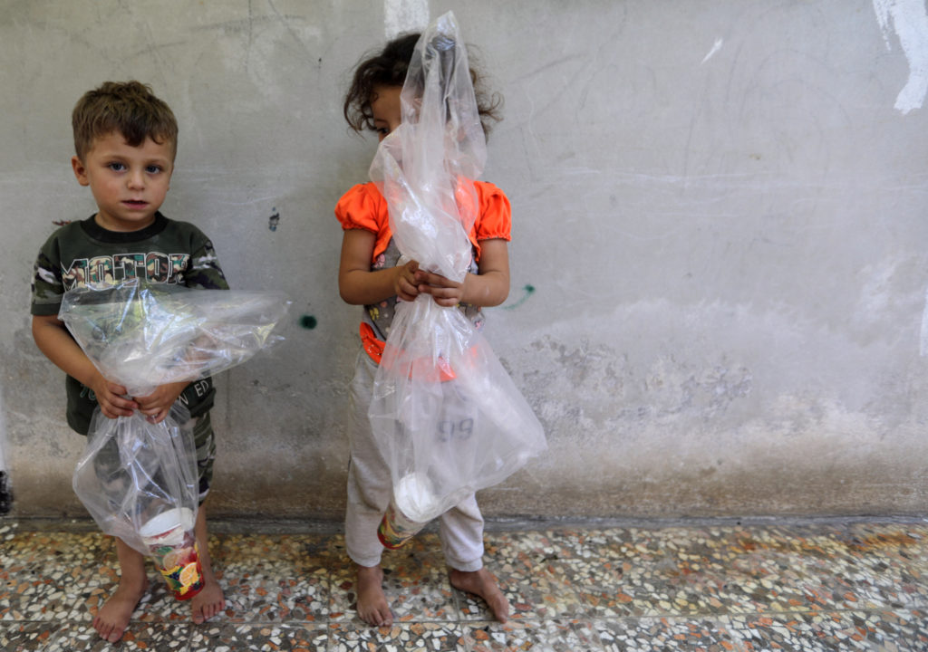 Children hold improvised gas masks made from plastic bags and paper cups in Idlib, Syria. Photo by Khalil Ashawi/Reuters