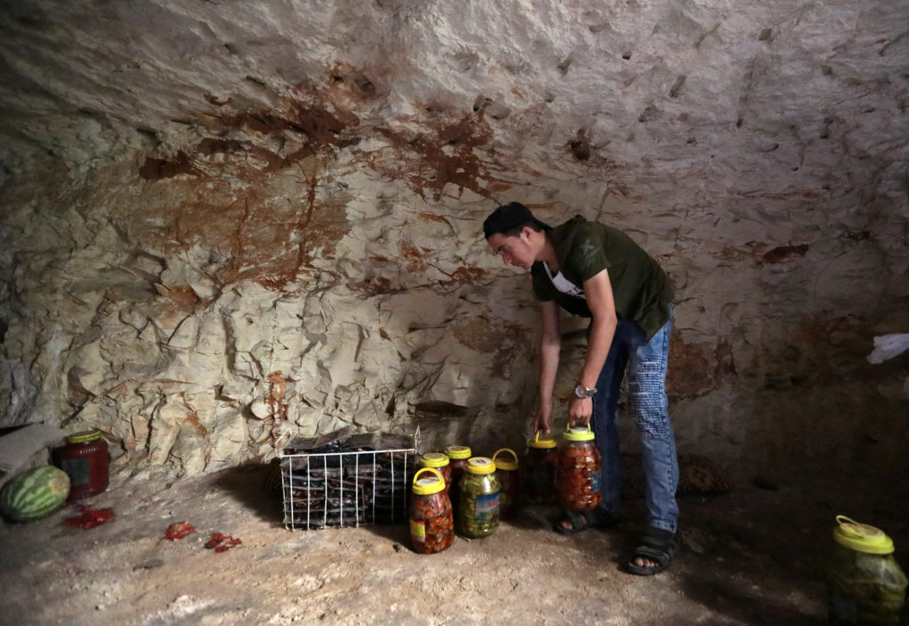 A man stores pickled vegetables in an underground cave in Idlib in case bombing starts on the rebel stronghold. Photo by Khalil Ashawi/Reuters