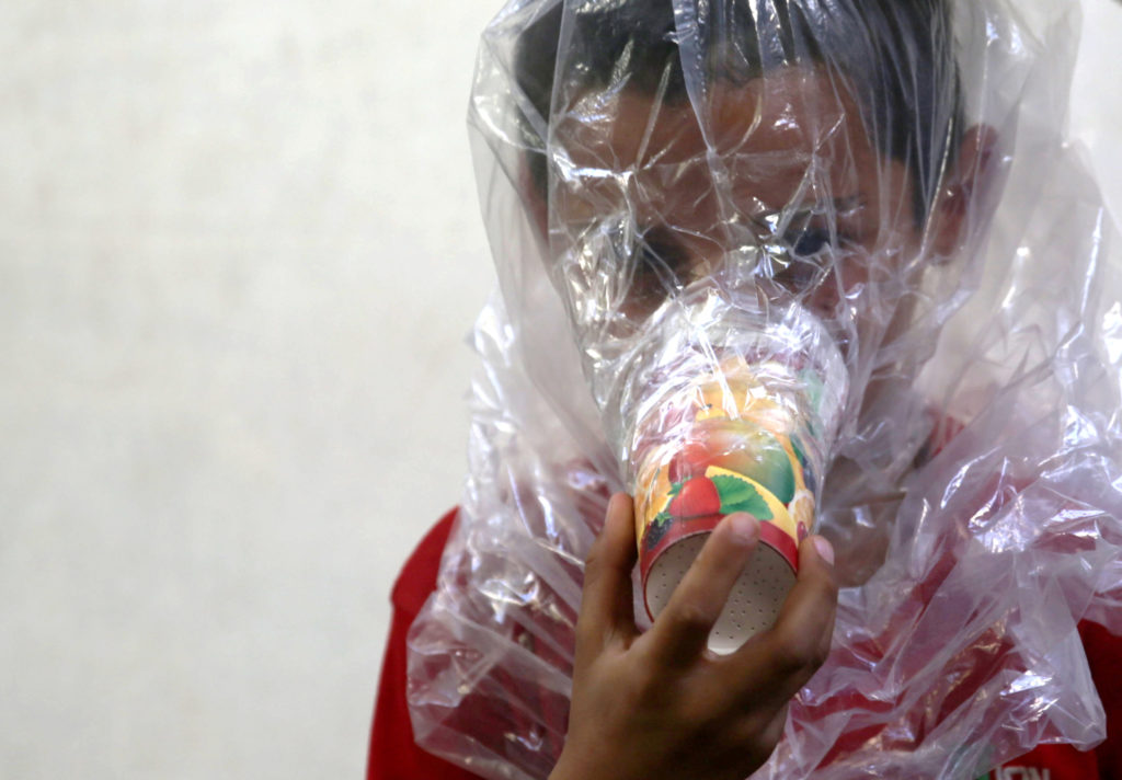 A boy tries on a homemade gas mask before an anticipated offensive on Idlib. Photo by Khalil Ashawi/Reuters