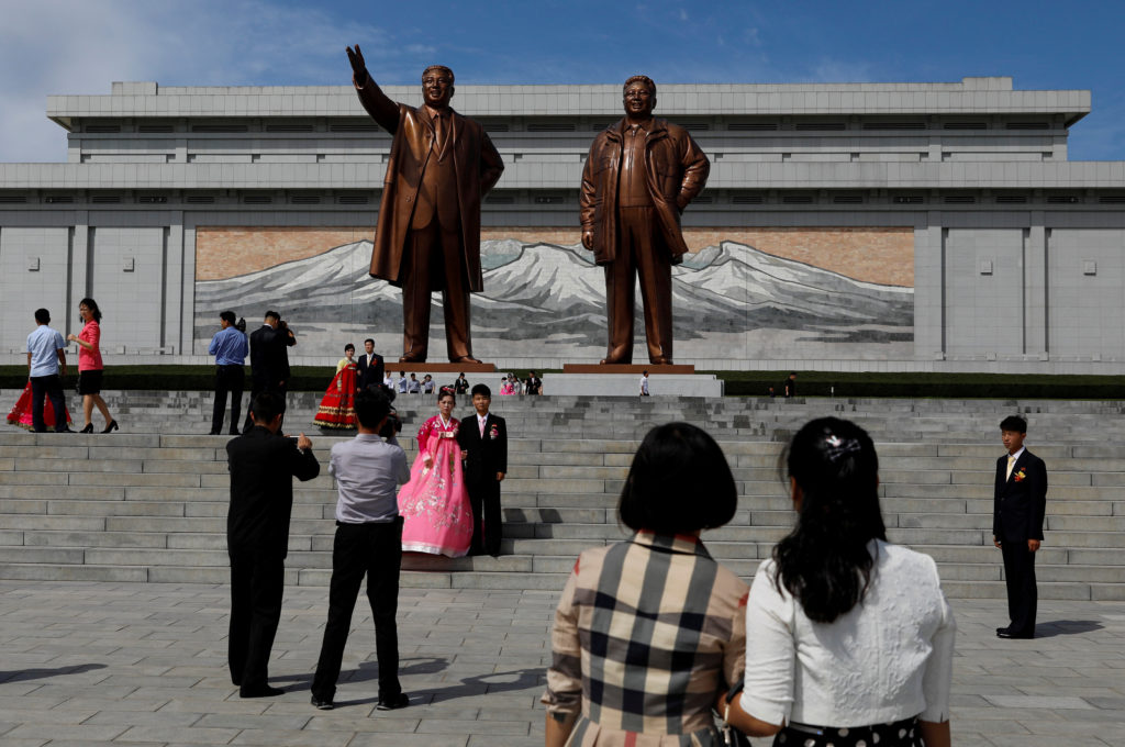 People pose in front of bronze statues of the late leaders Kim Il Sung and Kim Jong Il in Pyongyang, North Korea, on Sept. 11, 2018. Photo by Danish Siddiqui/Reuters