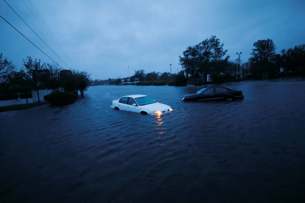 An abandoned car's hazard lights continue to flash in rising flood waters after Hurricane Florence struck in Wilmington, North Carolina. Photo by Jonathan Drake/Reuters