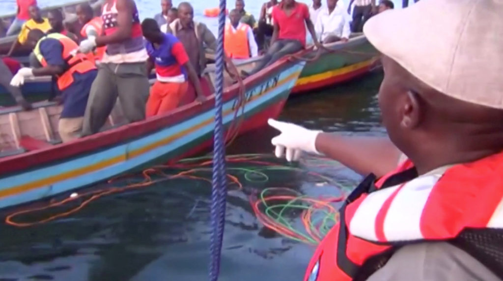 Rescue workers are seen at the scene where a ferry overturned in Lake Victoria, Tanzania, in this still image taken from video. Image via Reuters TV