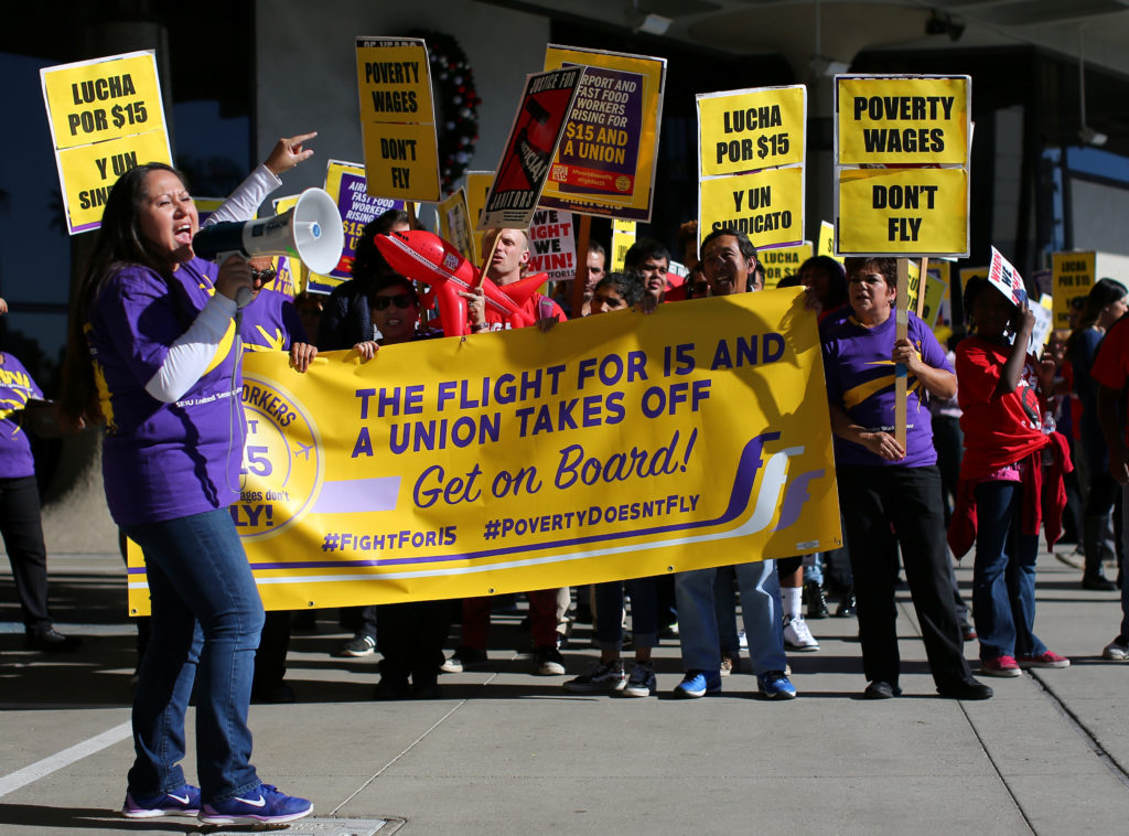 """Demonstrators participate in a """"Fight for $15"""" wage protest at San Diego's international airport Lindberg Field in San Diego, California, U.S., November 29, 2016. REUTERS/Mike Blake"""