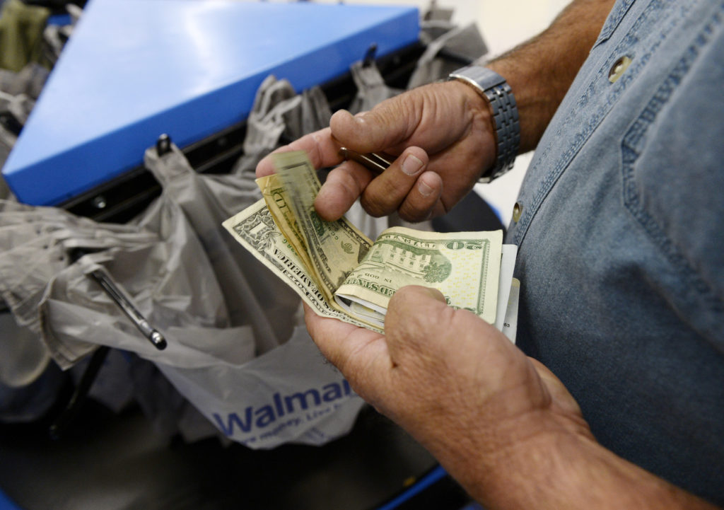 A customer counts his cash at the checkout lane of a Walmart store in the Porter Ranch section of Los Angeles. REUTERS/Kev...