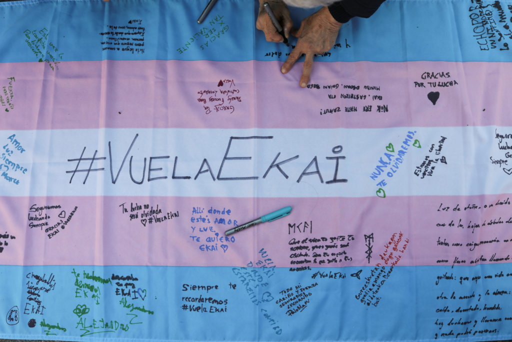 "People write messages on a transgender flag during a February gathering to remember 16-year-old transgender boy Ekai, who committed suicide, in Madrid, Spain. The writing means ""Fly Ekai."" Photo by Susana Vera/Reuters"