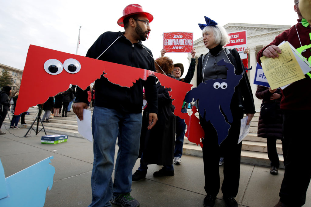 Demonstrators rally with cut-outs of congressional districts in front of the Supreme court before oral arguments on Benise...