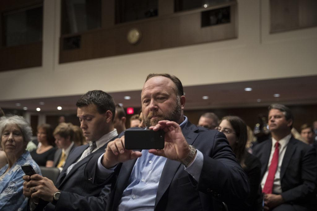 WASHINGTON, DC - SEPTEMBER 5: Alex Jones of InfoWars live streams on his phone during a Senate Intelligence Committee hear...