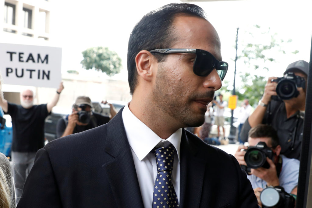 A protester holds a banner as former Trump campaign aide George Papadopoulos arrives for his sentencing hearing at U.S. Di...