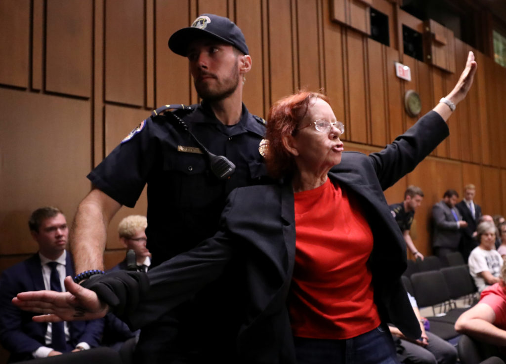 Police remove a protester during U.S. Supreme Court nominee judge Brett Kavanaugh's Senate Judiciary Committee confirmation hearing on Capitol Hill in Washington, U.S., September 5, 2018. REUTERS/Chris Wattie
