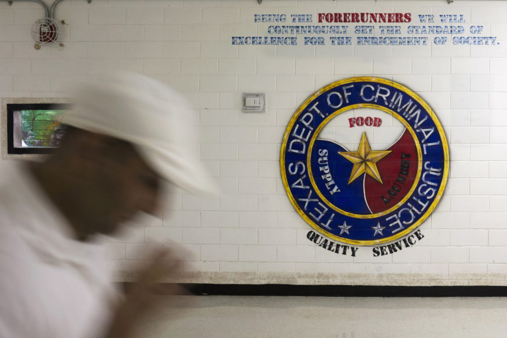 An offender walks past a sign on a wall at the the Darrington Unit of the Texas Department of Criminal Justice men's prison in Rosharon, Texas August 12, 2014. The Southwestern Baptist Theological Seminary, a private college based in Fort Worth, Texas, began its bachelor of science in biblical studies program at Darrington, south of Houston, about three years ago. To be accepted, an offender has to be at least 10 years from the possibility of parole, have a good behavior record and the appropriate academic credentials to enroll in a college course. The program, which is largely paid for by charitable contributions from the Heart of Texas Foundation, has more than 150 prisoners enrolled and plans to send its graduates as field ministers to other units who want the bible college alumni for peer counseling and spiritual guidance. The first degrees are expected to be conferred next year. Picture taken August 12, 2014.REUTERS/Adrees Latif