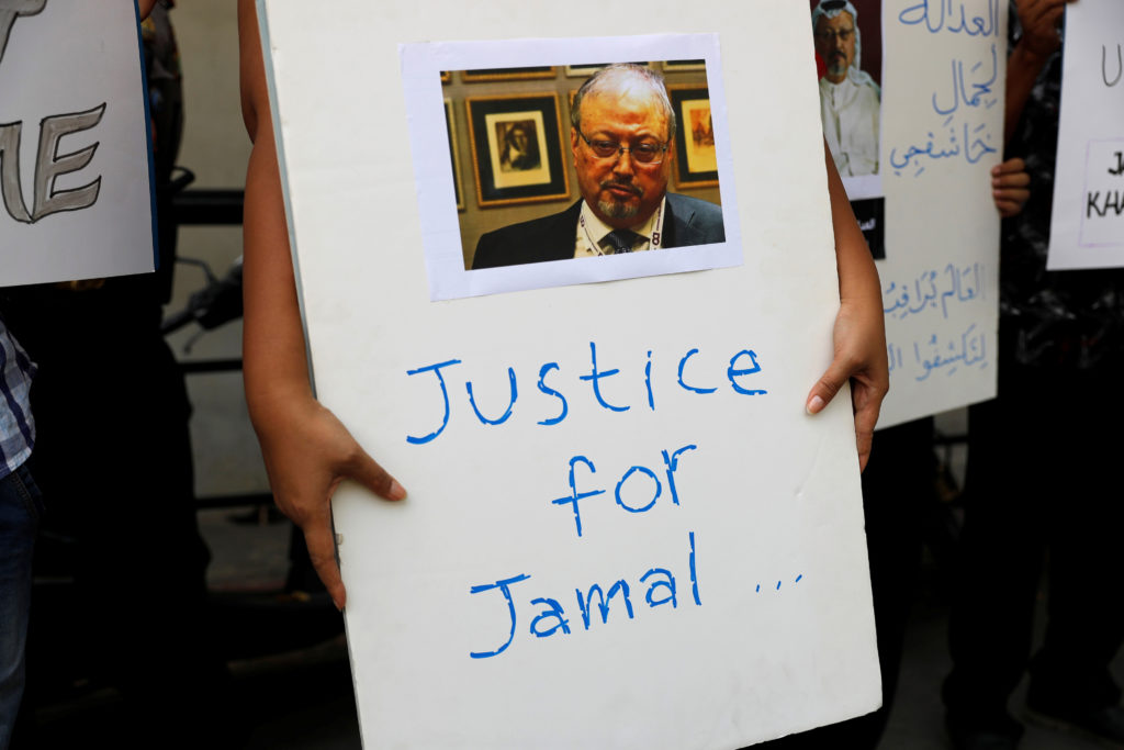 An Indonesian journalist holds a placard during a protest over the killing of Saudi journalist Jamal Khashoggi in front of...