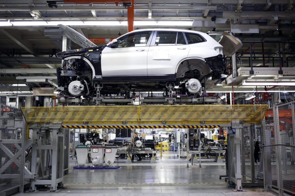 A Bayerische Motoren Werke AG (BMW) sports utility vehicle (SUV) sits on a platform during assembly at the BMW Manufacturi...