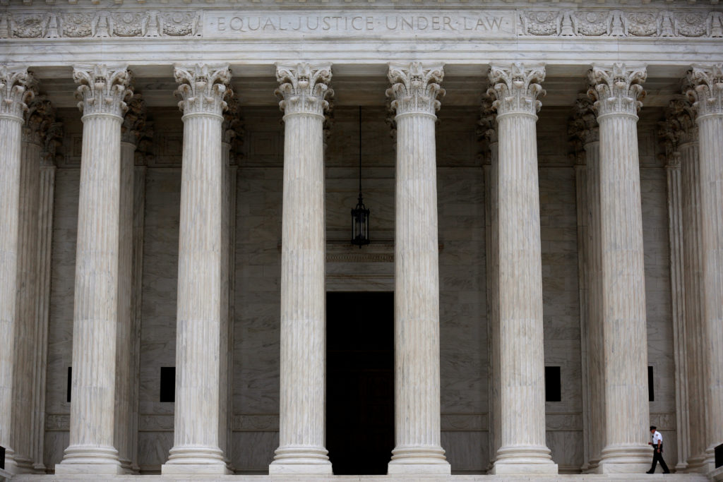 A police officer walks by columns of the Supreme Court in Washington, D.C. Photo by Joshua Roberts/Reuters