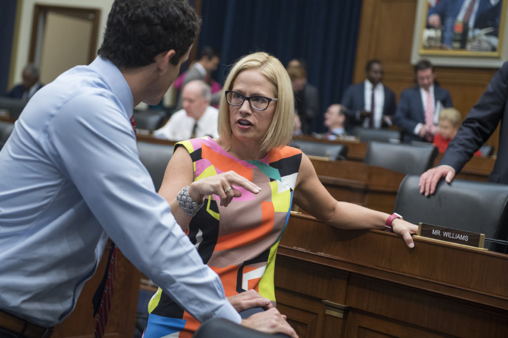 UNITED STATES - JUNE 21: Reps. Kyrsten Sinema, D-Ariz., and Trey Hollingsworth, R-Ind., talk before a House Financial Services Committee hearing in Rayburn Building titled Oversight of the U.S. Securities and Exchange Commission on June 21, 2018. (Photo By Tom Williams/CQ Roll Call)