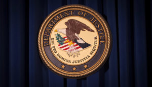 The Department of Justice (DOJ) logo is pictured on a wall after a news conference in New York December 5, 2013. Photo by REUTERS/Carlo Allegri