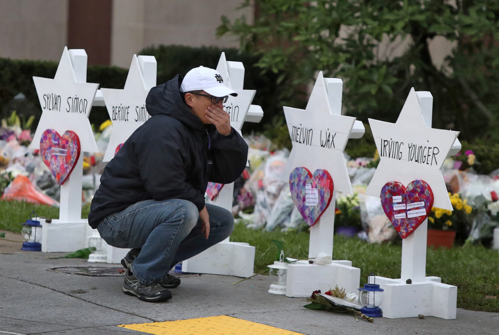 A man reacts at a makeshift memorial outside the Tree of Life synag…