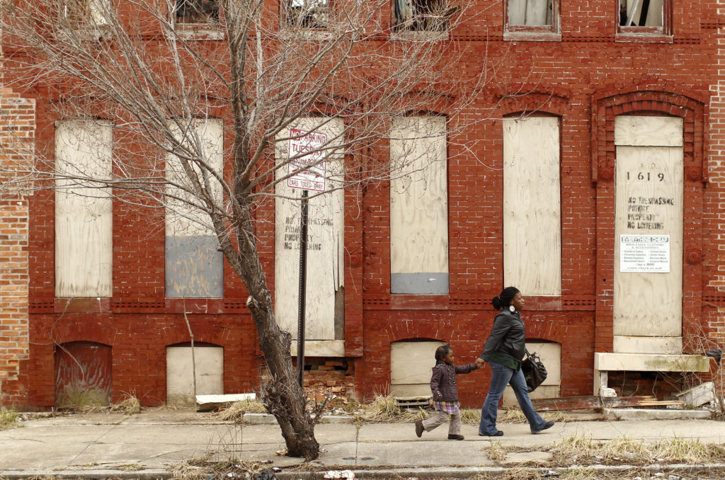 A woman and child walk past a dilapidated building in a run-down neighborhood of Baltimore, Maryland. New research suggest...