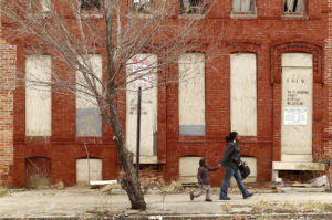 A woman and child walk past a dilapidated building in a run-down neighborhood of Baltimore, Maryland. New research suggests that impoverished Americans are getting left out even when their communities enjoy hiring booms. Photo by Kevin Lamarque/Reuters