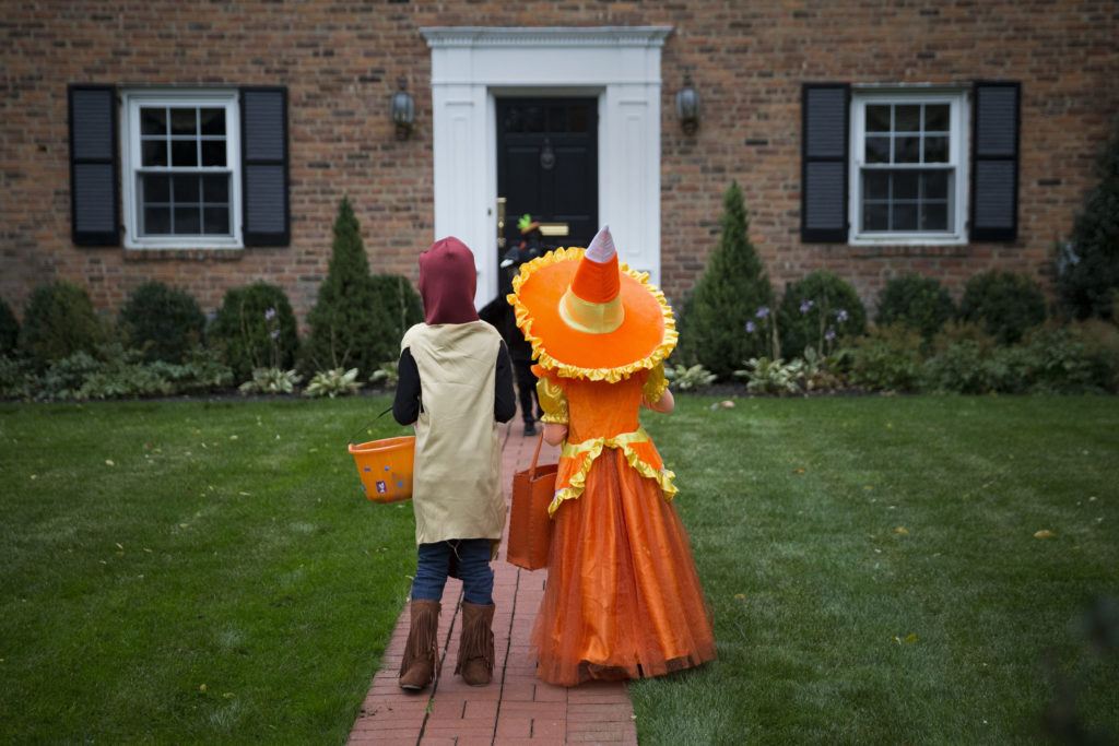 Kids dressed in costumes wait for candy while trick or treating during Halloween in Port Washington, New York, October 31, 2014. Photo by Shannon Stapleton/Reuters