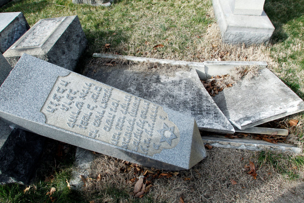 A headstone, pushed off its base by vandals, lays on the ground near a smashed tomb in the Mount Carmel Cemetery, a Jewish...