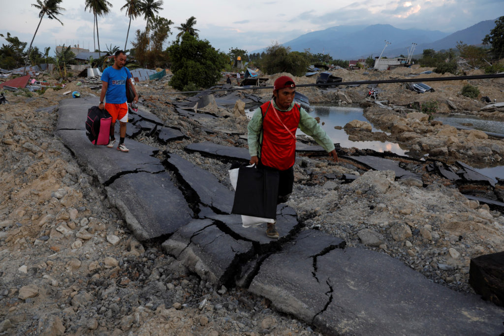 Residents carry their belongings on Oct. 1 after an earthquake Palu, Sulawesi Island, Indonesia on Friday. Photo by Beawiharta/Reuters