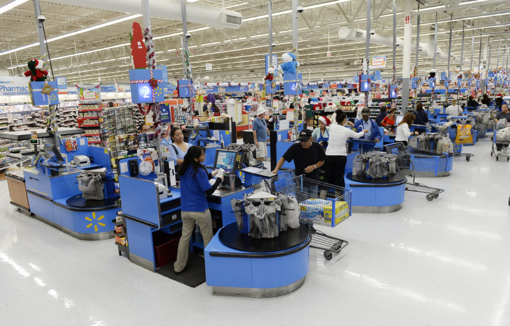 Cashiers work at the checkout lanes of a Walmart store in Los Angeles in 2013. Photo by Kevork Djansezian/Reuters