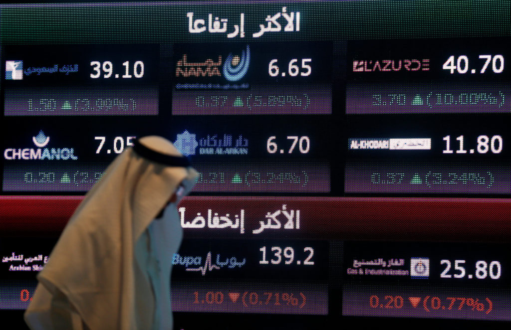 An investor walks past a screen displaying stock information at the Saudi Stock Exchange in Riyadh. Investors have dumped more than $1 billion worth of Saudi stocks in response to Jamal Khashoggi's death. Photo by Faisal Al Nasser/Reuters