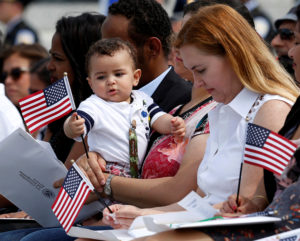 A baby plays with a U.S. flag at a naturalization ceremony for new U.S. citizens at the WWII Memorial in Washington, D.C. President Donald Trump suggested this week that he might try to change U.S. law that gives automatic citizenship to children born on U.S. soil. Photo by Gary Cameron/Reuters