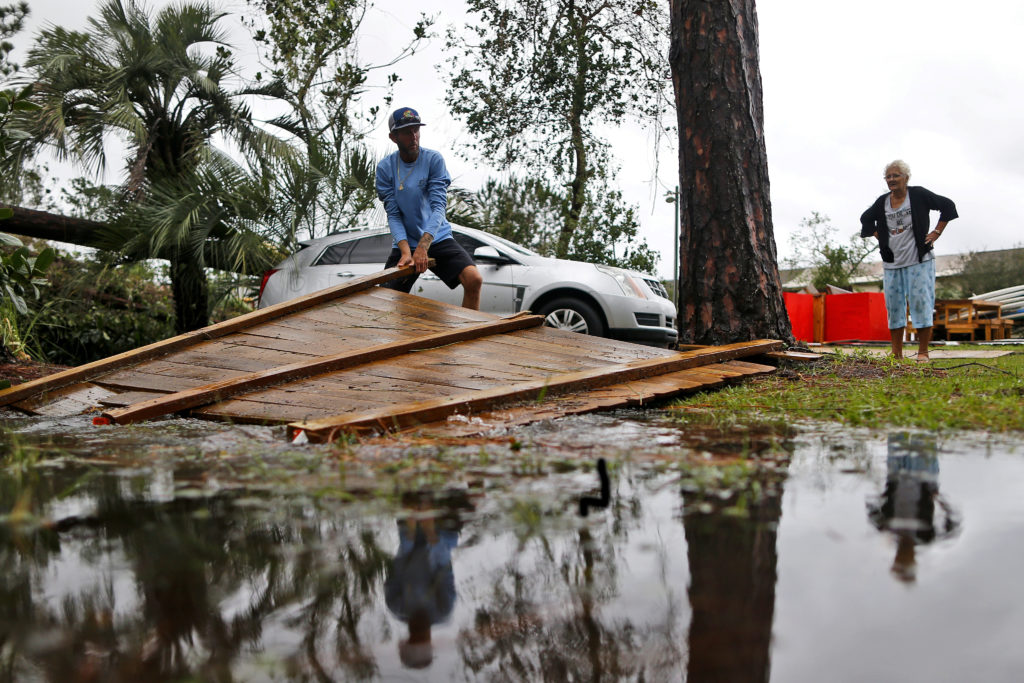 Joseph Howat clears a damaged fence by Hurricane Michael at his business in Panama City Beach, Florida. Photo by Jonathan Bachman/Reuters