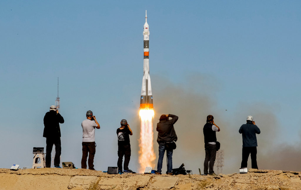 Photographers take pictures as the Soyuz MS-10 spacecraft carrying U.S. astronaut Nick Hague and Russian cosmonaut Alexey Ovchinin blasts off to the International Space Station from the launchpad at the Baikonur Cosmodrome in Kazakhstan on Oct. 11. Photo by Shamil Zhumatov/Reuters