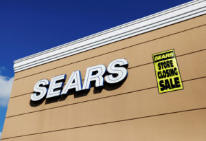 A store closing sale sign is posted next to a Sears logo in New Hyde Park, New York. Photo by Shannon Stapleton/Reuters