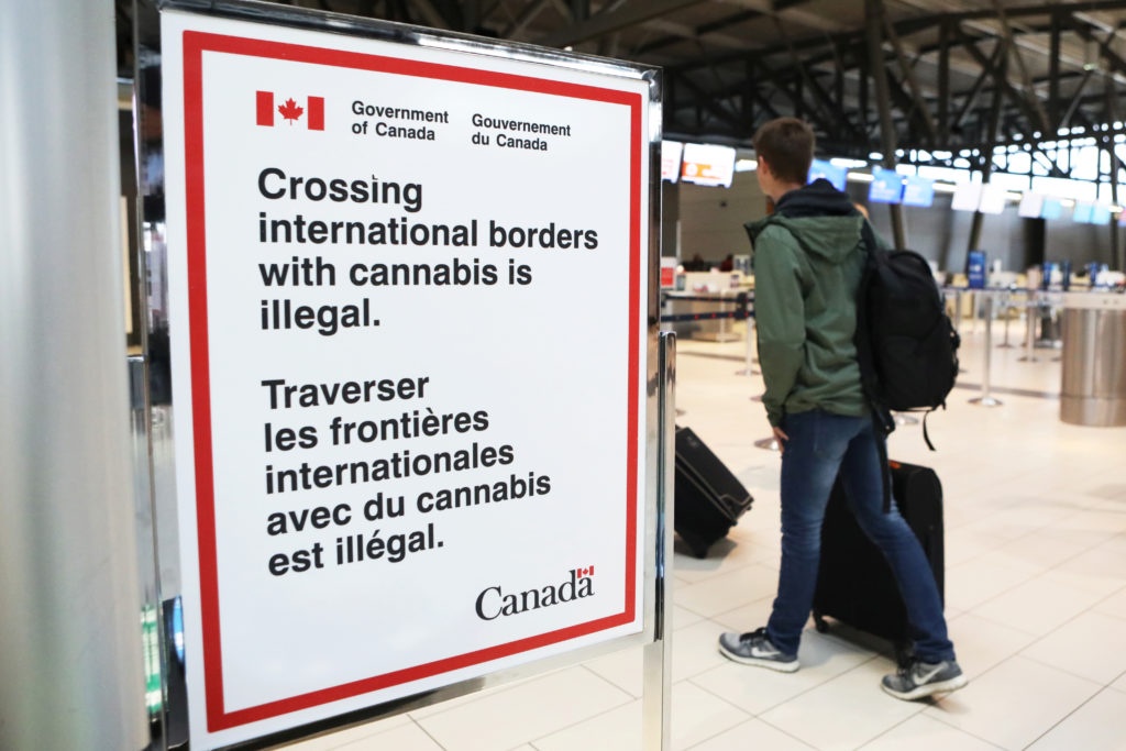 A sign warning travelers about crossing international borders with cannabis is seen at the Ottawa International Airport. Because marijuana is still illegal at the federal level in the U.S., the Canadian and U.S. markets are still largely divided. Photo by Chris Wattie/Reuters