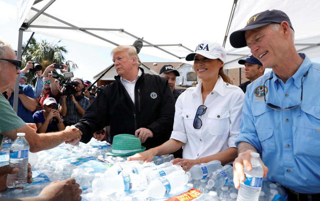 President Donald Trump, first lady Melania Trump and Florida Governor Rick Scott (R) help distribute water in the town of Lynn Haven, Florida, during a tour of areas ravaged by Hurricane Michael in Florida. Photo by Kevin Lamarque/Reuters