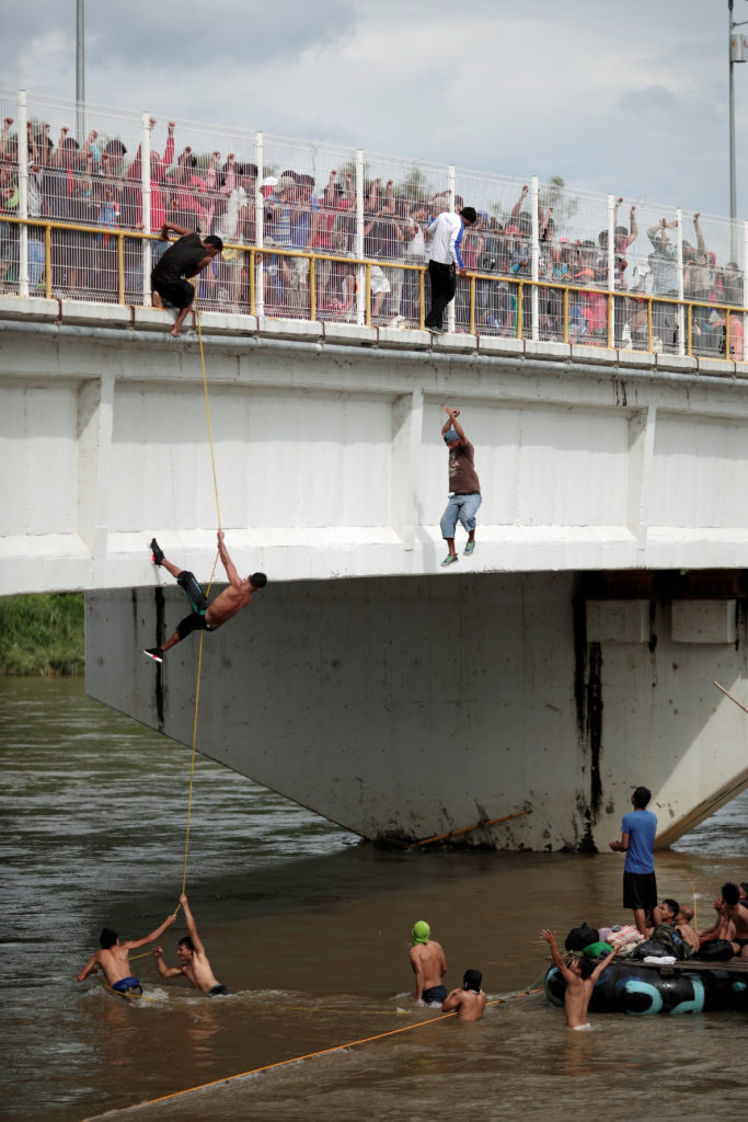 Migrants climb down from a bridge that connects Mexico and Guatemala on Oct. 19. Photo by Ueslei Marcelino/Reuters