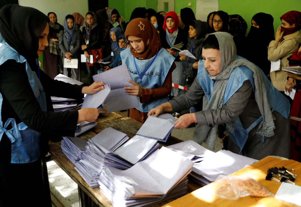 Afghan election workers count ballots during parliamentary elections at a polling station in Kabul on Oct. 21. Photo by Mohammad Ismail/Reuters