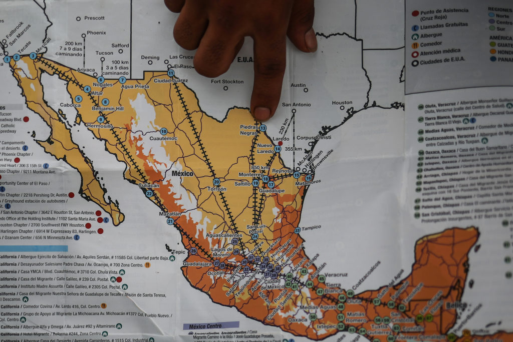 A man points at a map showing the routes through Mexico to the U.S. southern border. Photo by Adrees Latif/Reuters