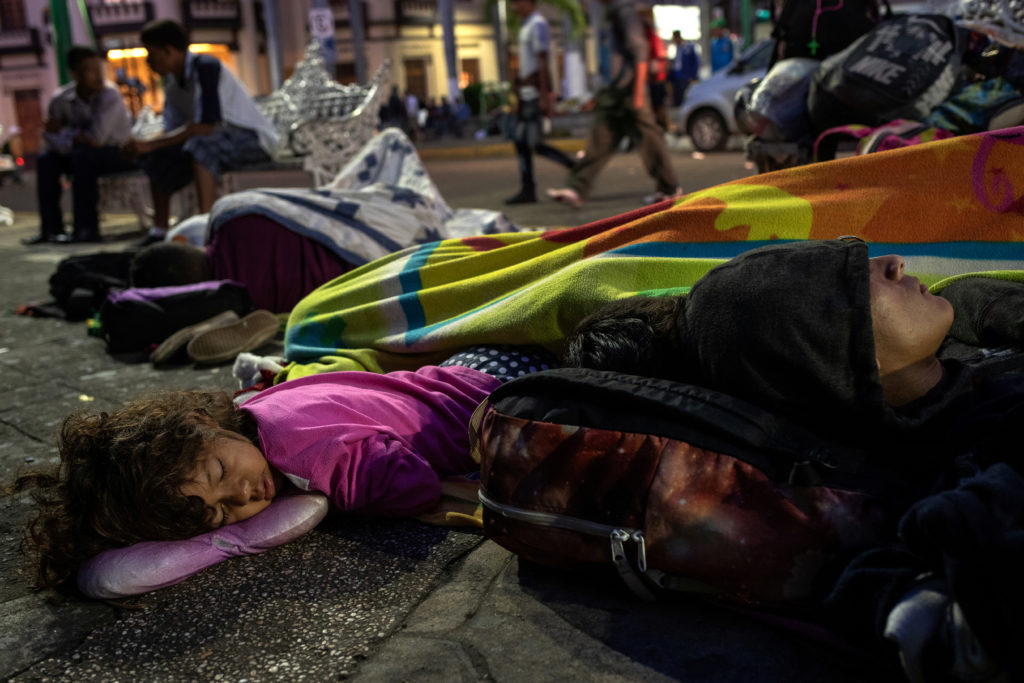 A family -- part of the caravan heading north -- sleeps along a sidewalk in the Tapachula city center in Mexico on Oct. 22. Photo by Adrees Latif/Reuters