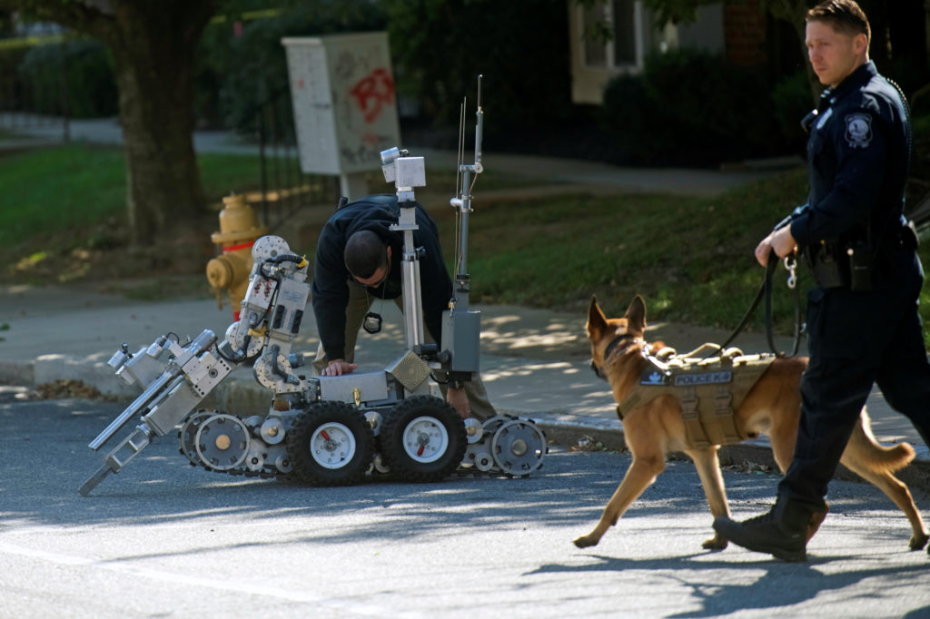 Law enforcement personnel and bomb disposal robot outside a post office which had been evacuated in Wilmington, Delaware, ...