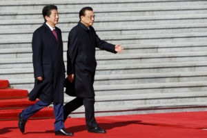 Japanese Prime Minister Shinzo Abe (left) and Chinese Premier Li Keqiang attend a ceremony outside the Great Hall of the People in Beijing, China on Oct. 26. Photo by Thomas Peter/Reuters