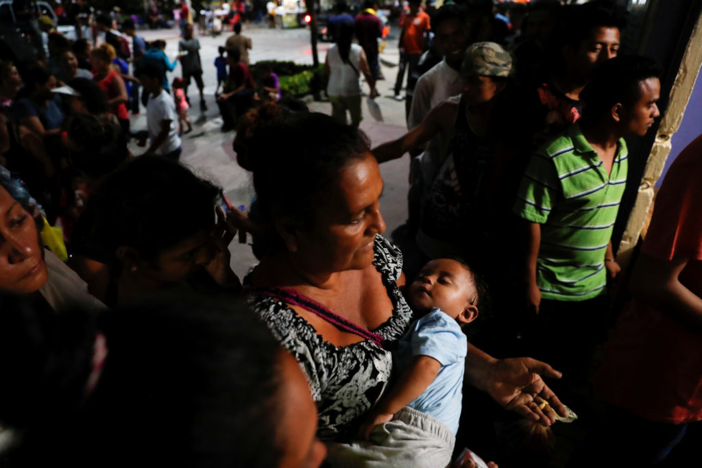 Eva Carrillo, migrant from Honduras, part of a caravan trying to reach the U.S., queues while carrying the baby of a friend, while she waits for food to be handed out at a church, in Tecun Uman, Guatemala October 26, 2018. Photo by Carlos Garcia Rawlins/Reuters