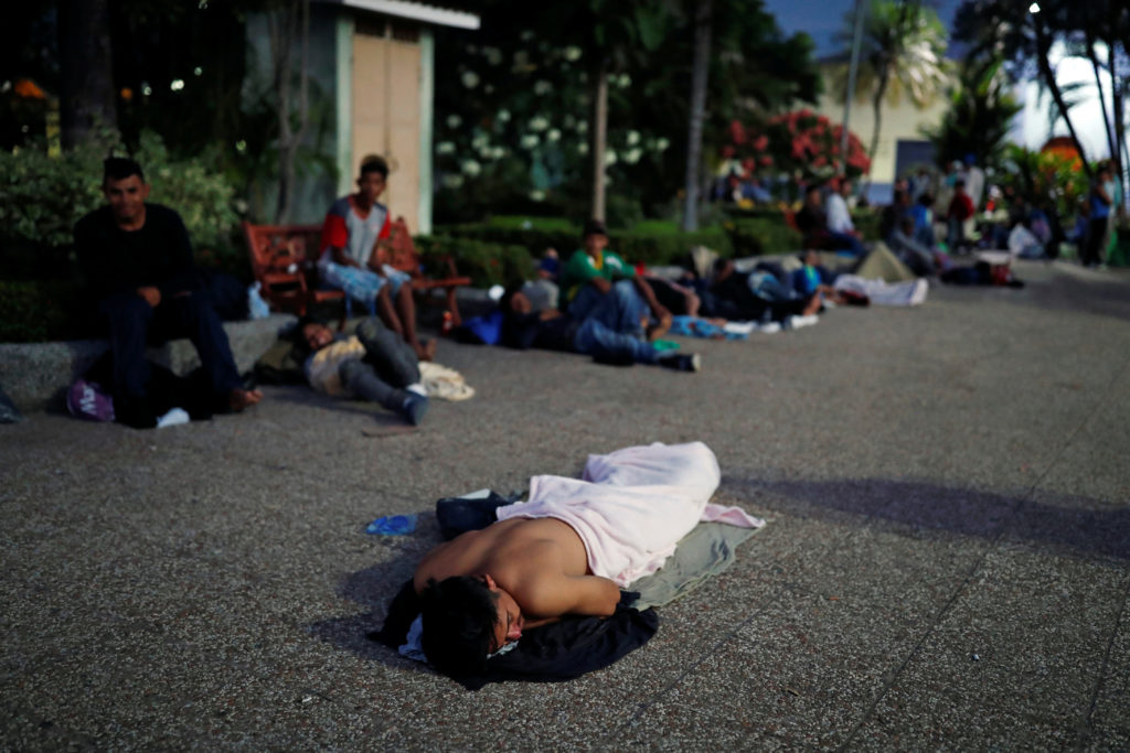 Central American migrant, part of a caravan trying to reach the U.S., sleeps on the pavement in Tecun Uman, Guatemala, October 27, 2018. REUTERS/Carlos Garcia Rawlins - RC162DBCB480