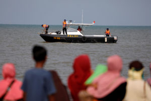 People watch rescue team members on a boat before they head to the Lion Air, flight JT610, sea crash location in the north coast of Karawang regency, West Java province, Indonesia. Photo by Beawiharta/Reuters